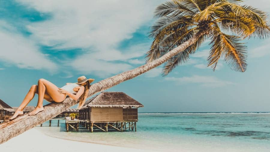 Woman laying on palm tree, Maldives