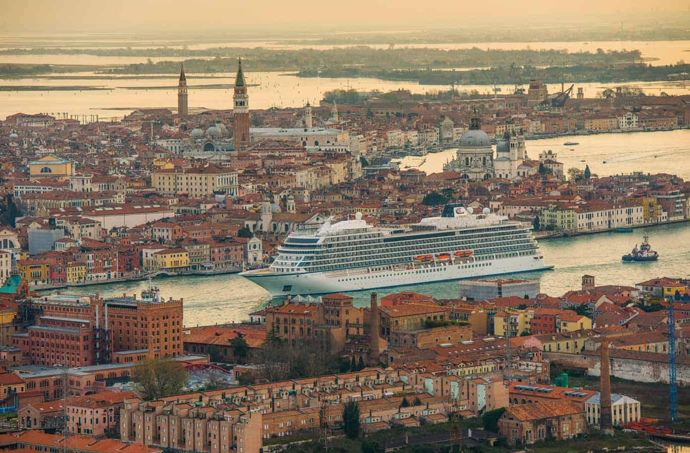 Cruise ship sailing through Venice at sunset.