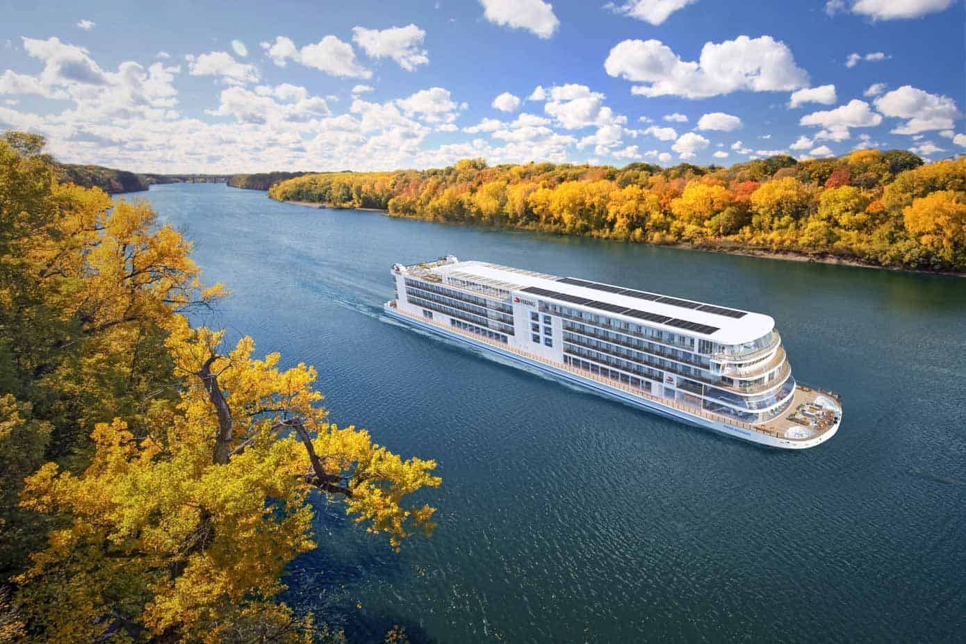 River cruise ship sailing down the Mississippi river on an autumn day.