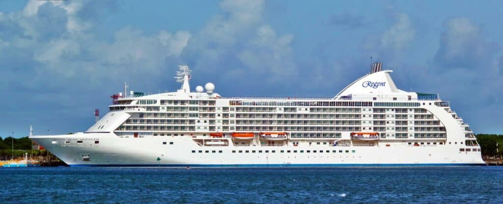 Full side view of a cruise ship sailing near land.