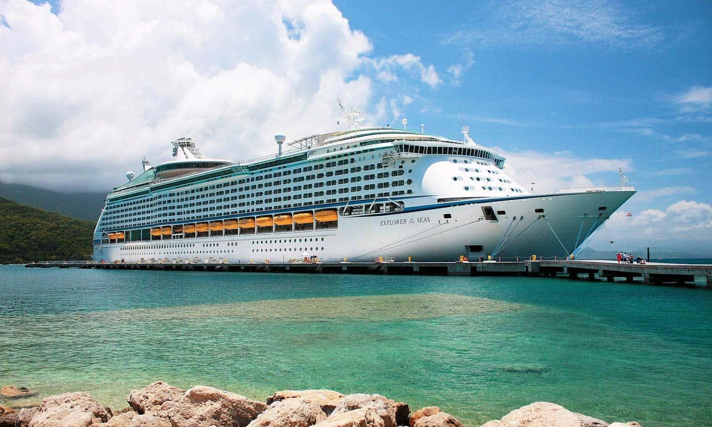 Royal Caribbean cruise ship at dock on a sunny day.