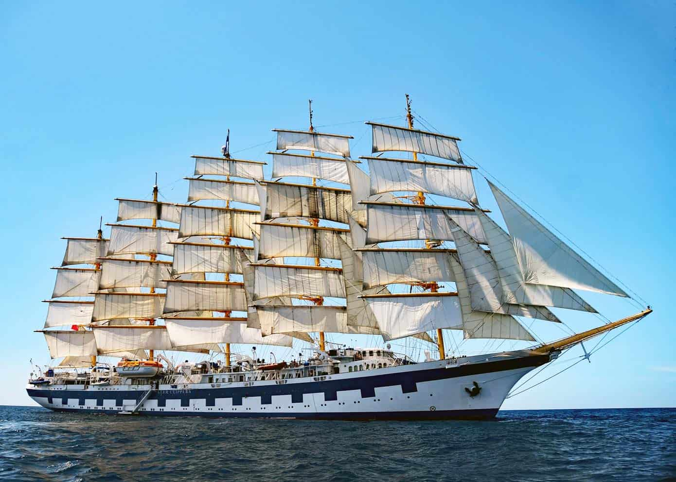 Large sailing ship in the ocean on a gorgeous day with blue skies.
