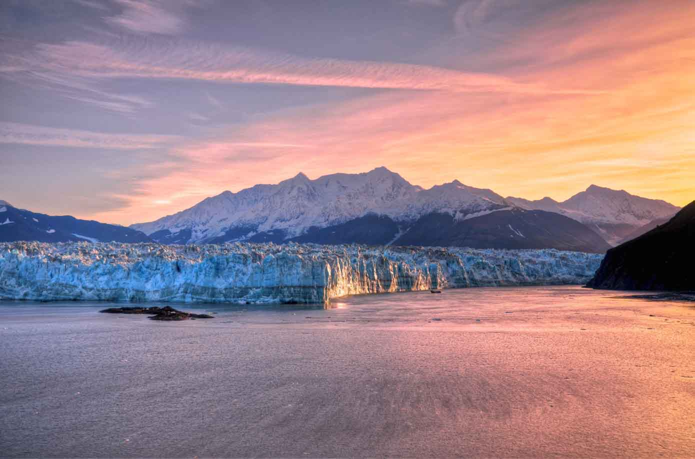 Sunrise as seen from the ocean peaking over a glacier in Alaska.