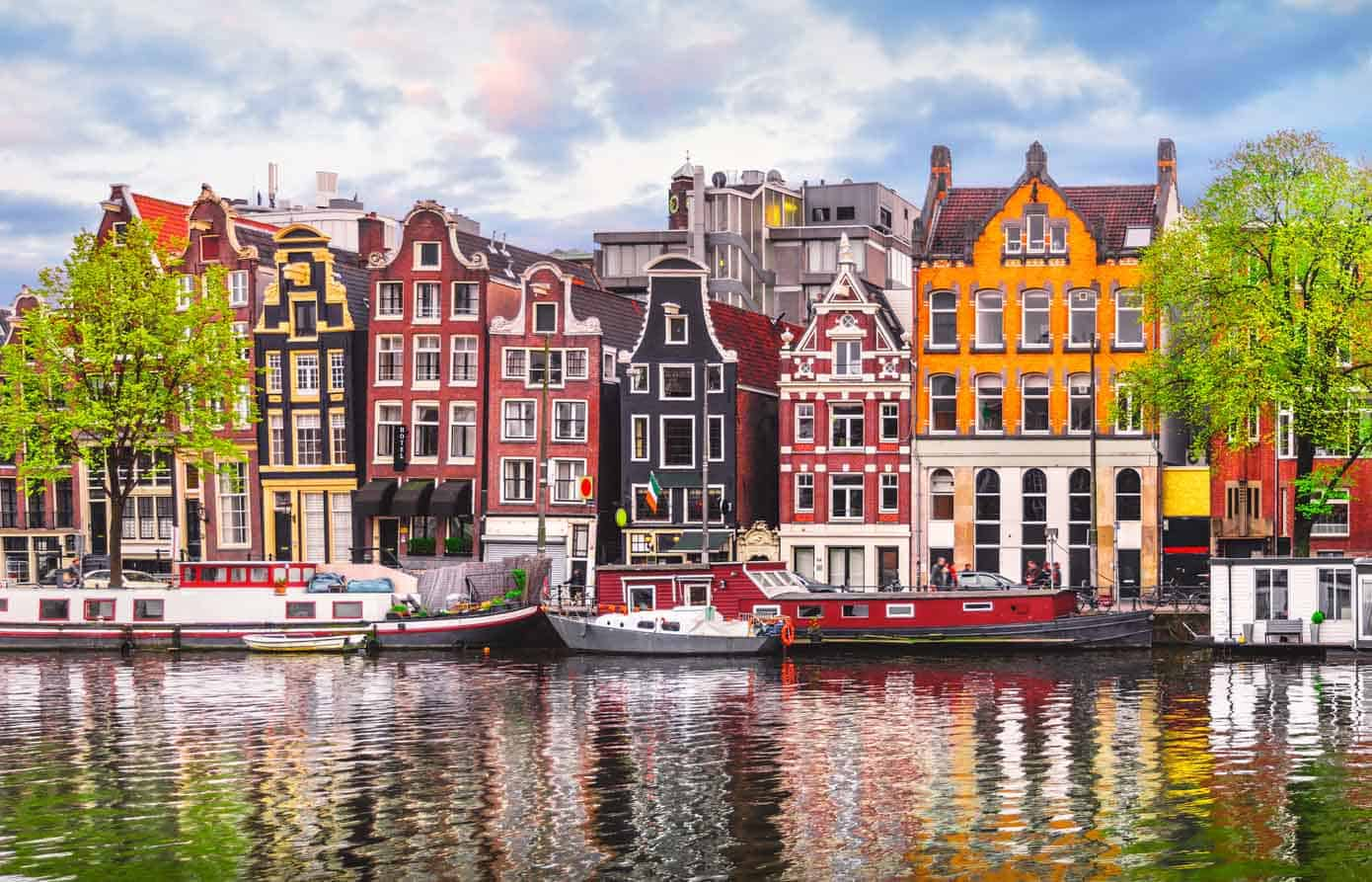 Colorful European houses lining the Amstel River in Amsterdam, Netherlands.