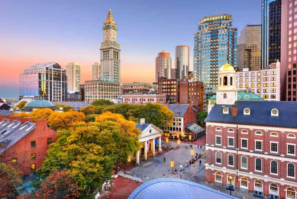 Skyline of Boston Massachusetts including Faneuil Hall and Quincy Market at dusk.