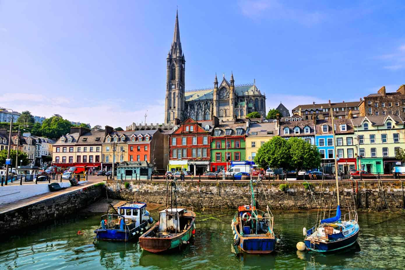 Colorful buildings and old boats with cathedral in background in the harbor of Cobh, County Cork, Ireland.