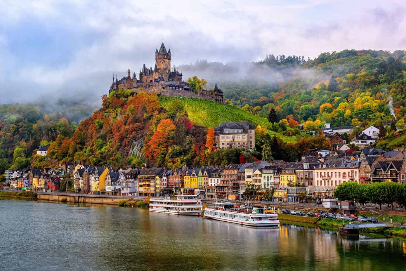 Reichsburg Castle on a hill along a river on a cloud day during autumn.