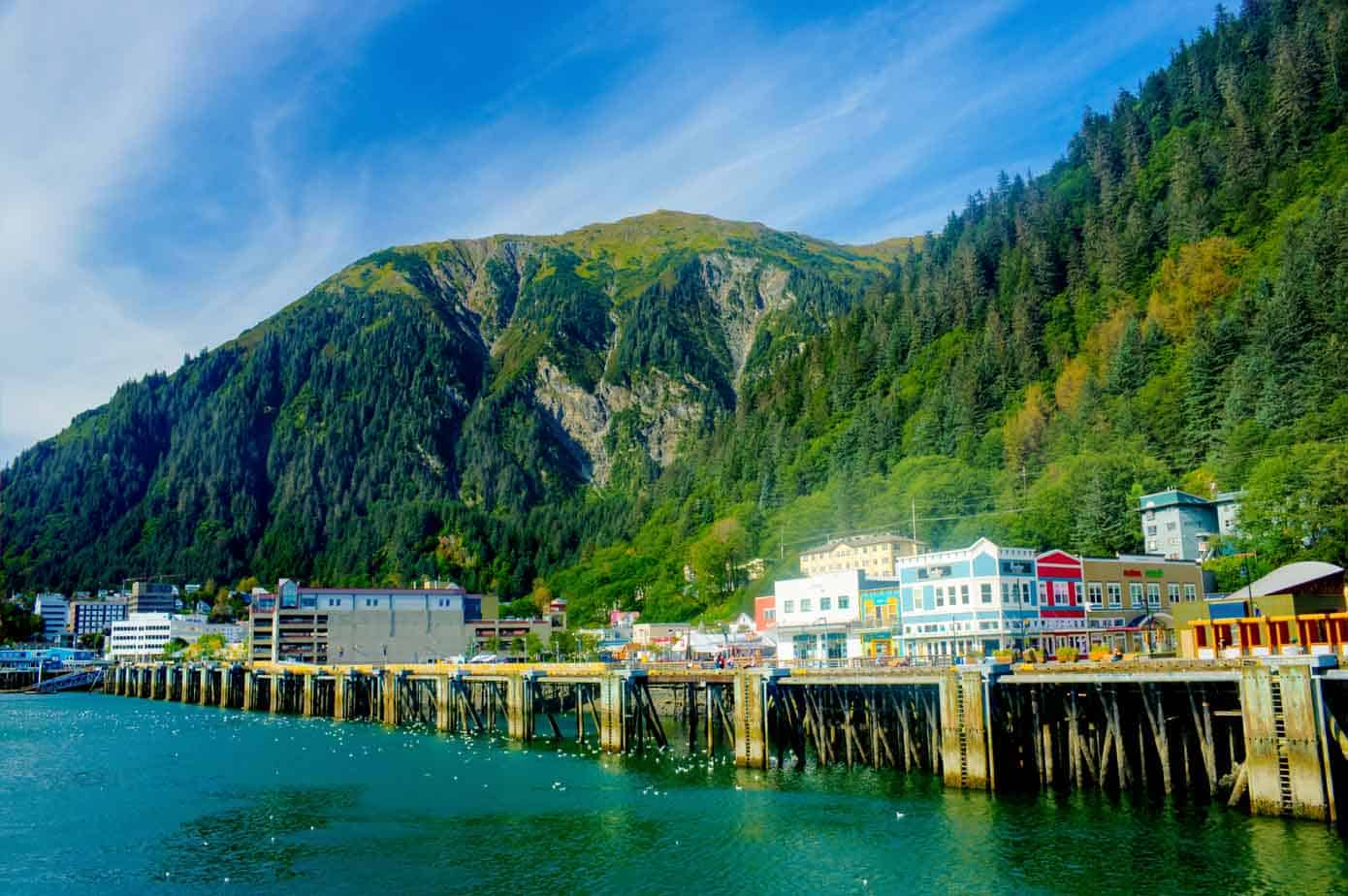 Dock on the ocean with lush mountains in background.