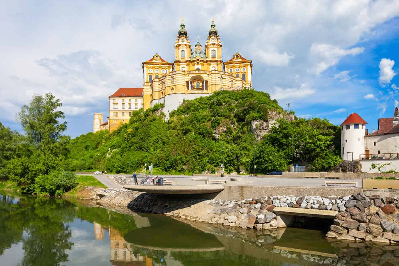Melk Abbey Monastery on a rocky outcrop overlooking the Danube River on a sunny day.