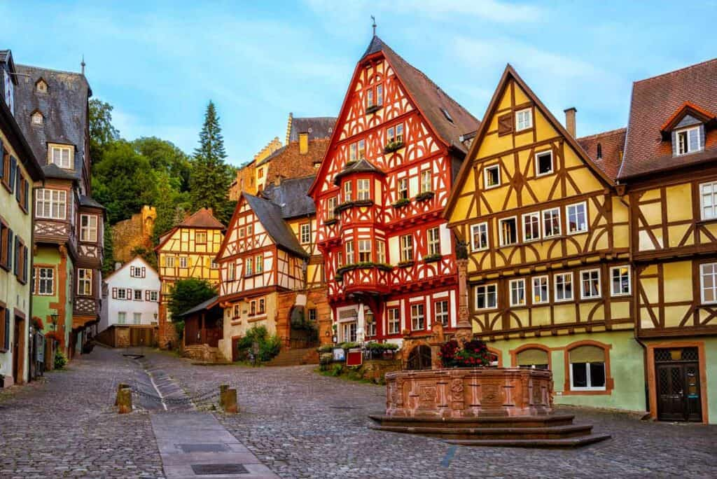 Colorful half-timbered houses on a cobblestone street in Bavaria, Germany.