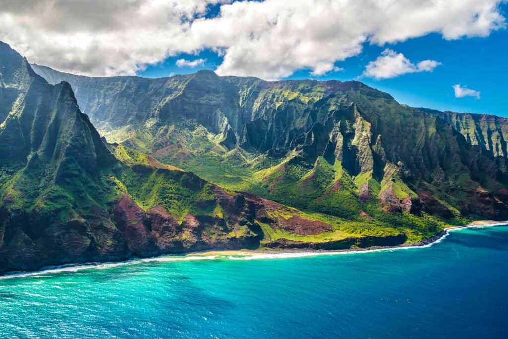 Majestic sea cliffs on the Napali Coast of Hawaii sloping into a bright blue ocean.