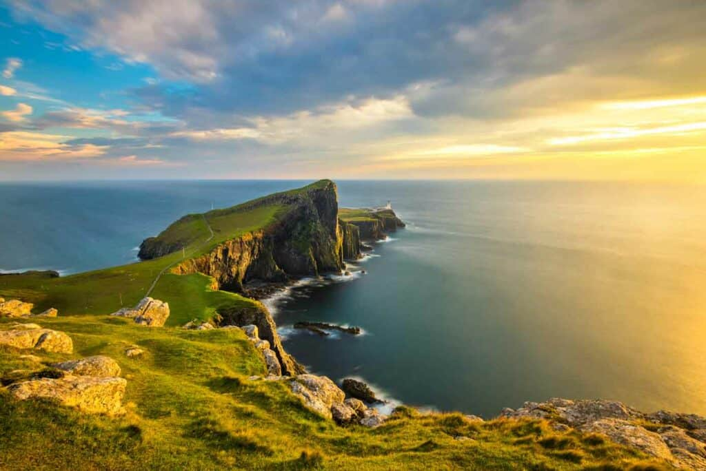 Cliffs with green grass jetting into the ocean during a beautiful sunset at Neist Point on the Isle of Skye, Scotland.
