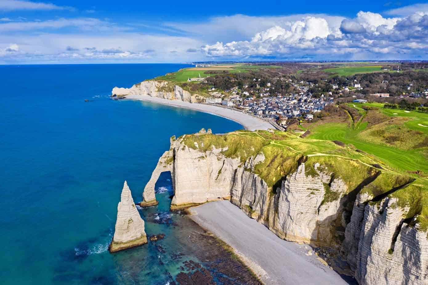 Huge cliffs, blue ocean, and spanning beaches with a little village in Normandy, France.