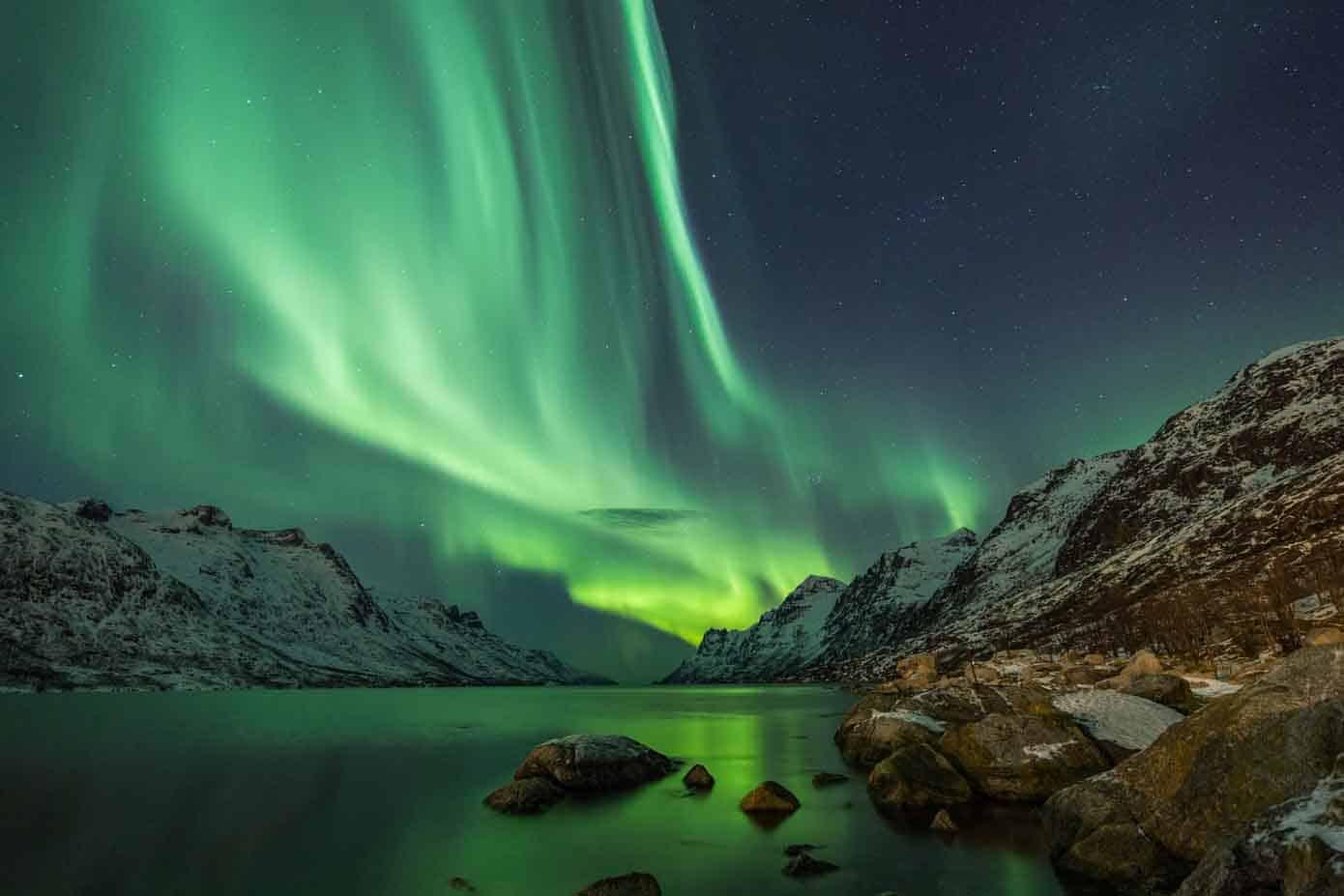 Northern lights between two fjords in Tromso, Norway.
