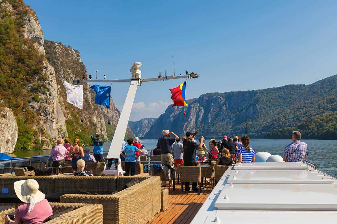 People on a river cruise ship taking pictures of large the Iron Gates gorge on the Danube River.