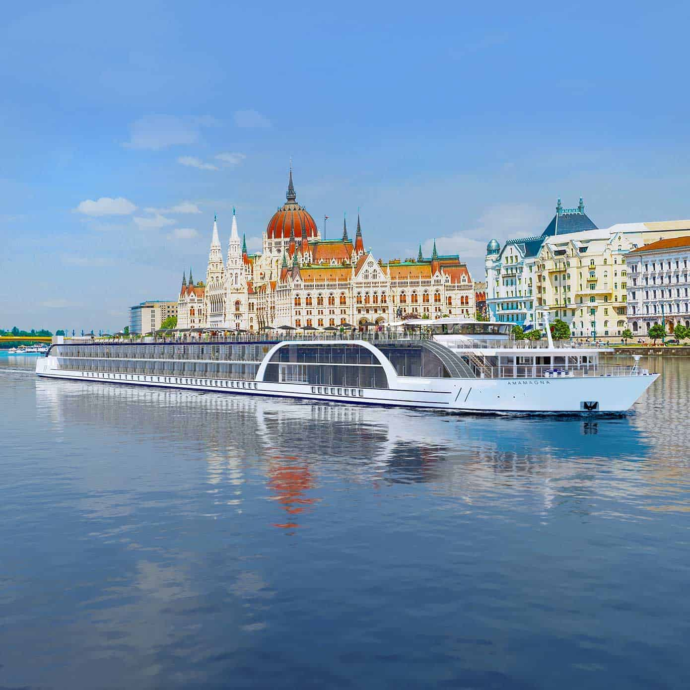 Exterior view of a river cruise ship with a historic city in the background.