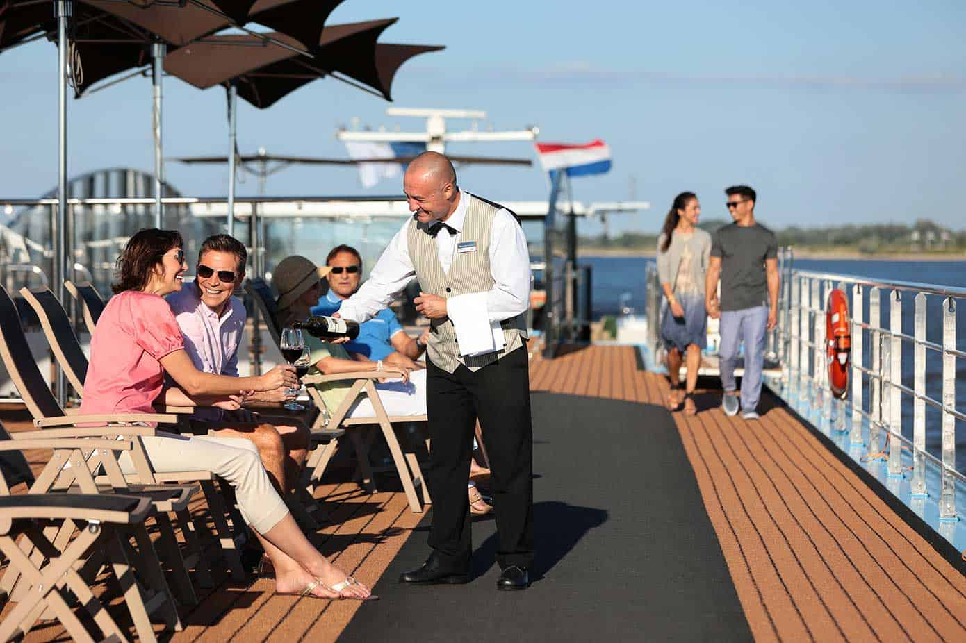 Waiter pouring a glass of wine for a couple on a river cruise ship on a sunny day.