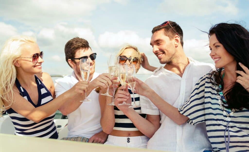 Group of adults celebrating and clinking glasses on a boat.