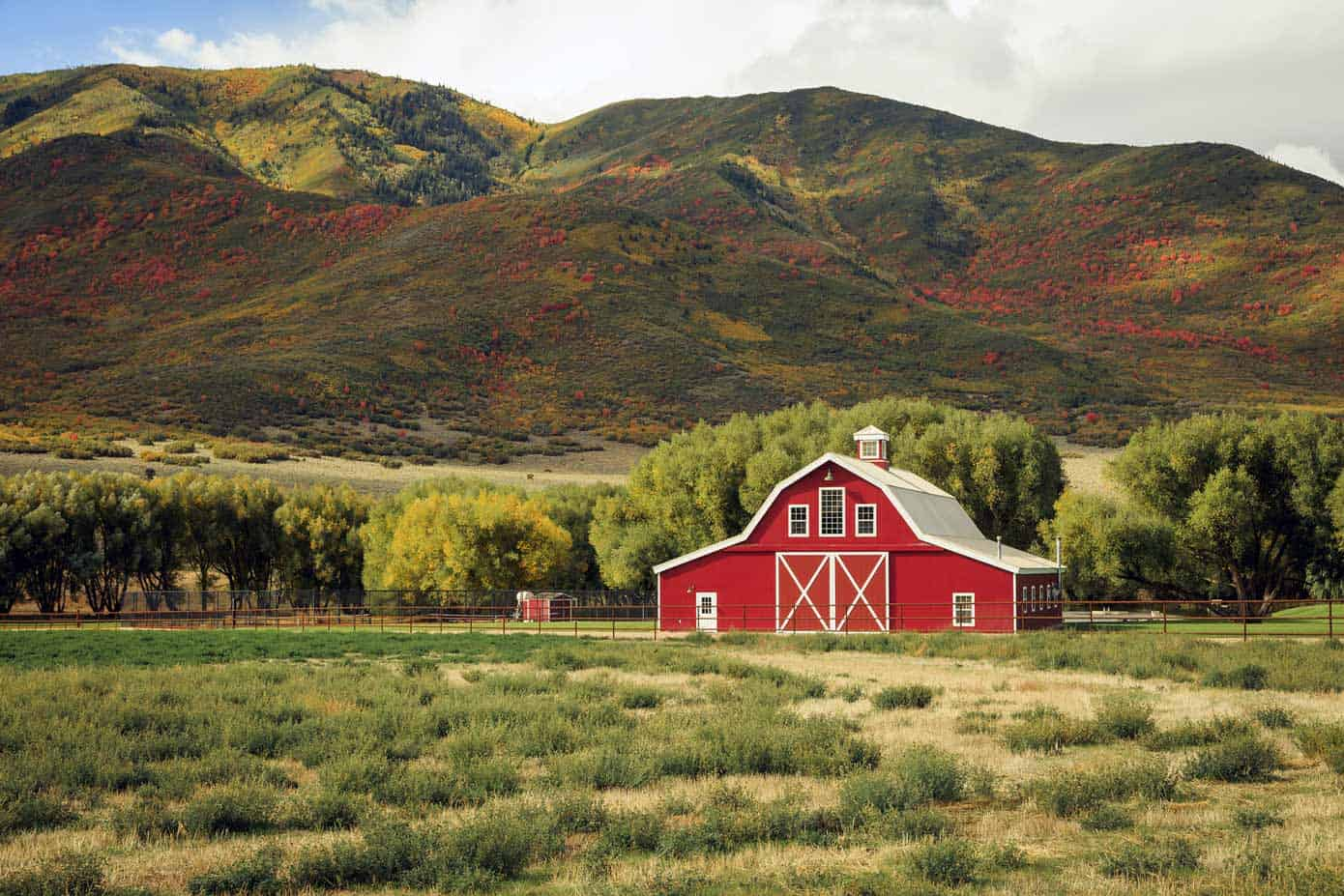Picturesque red barn with rolling hills in the background.