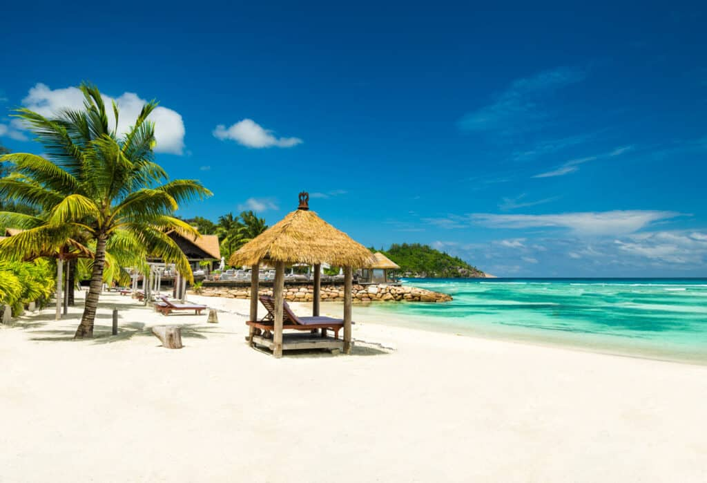 A sunny Caribbean beach with chairs, turquoise water and sapphire blue skies.