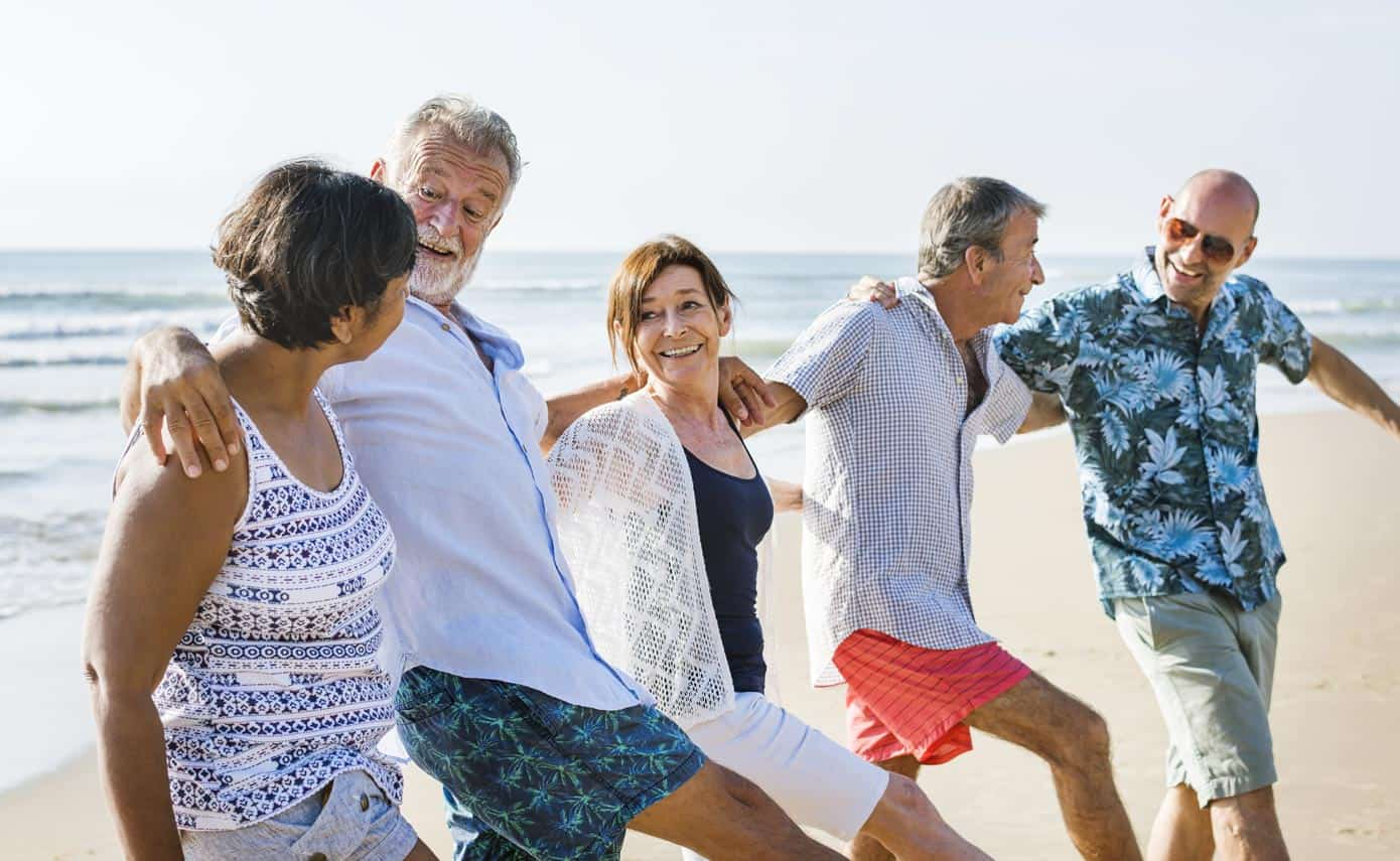 Group of older men and women celebrating on the beach.