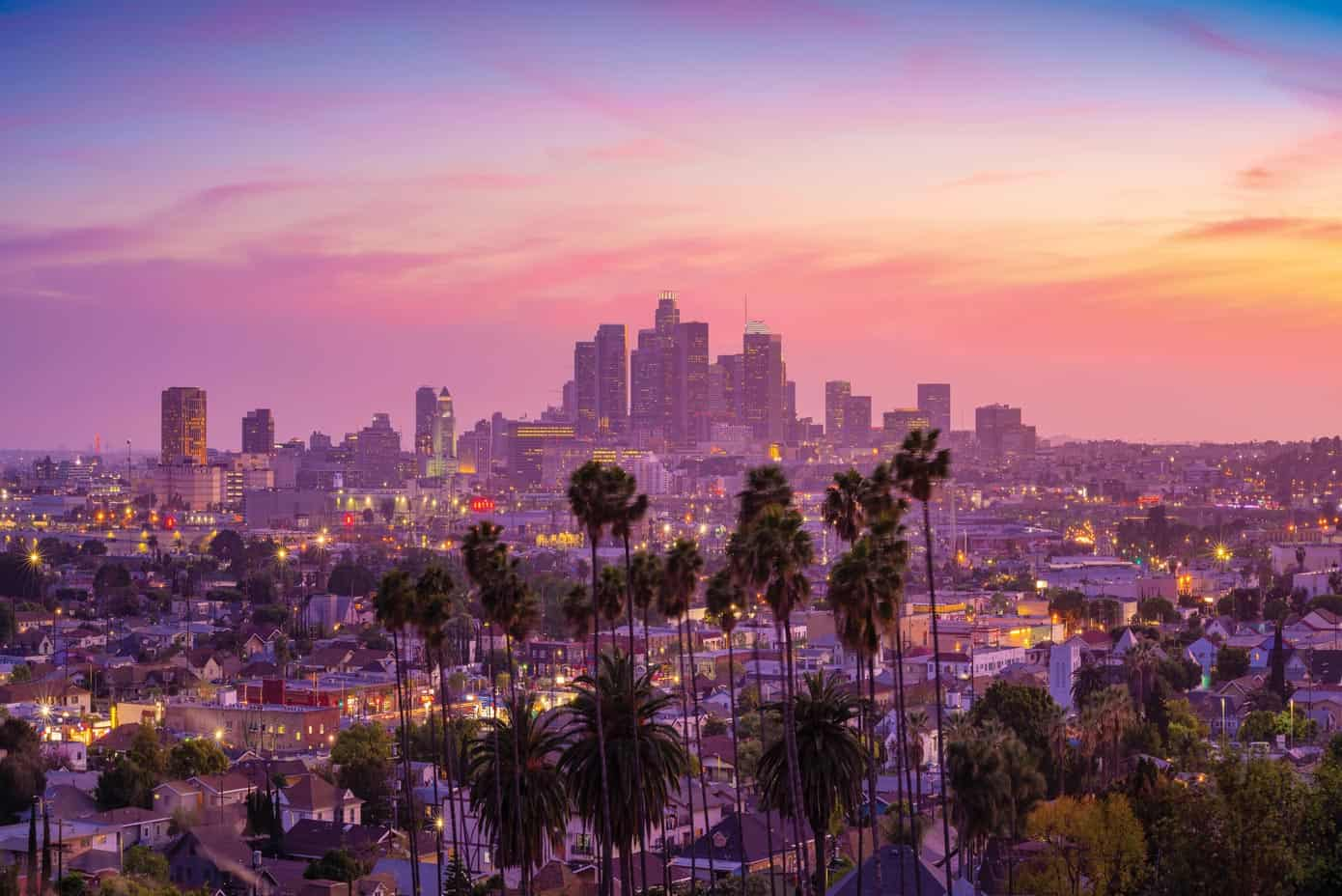 Stunning skyline and palm trees sunset view of Los Angeles, California.