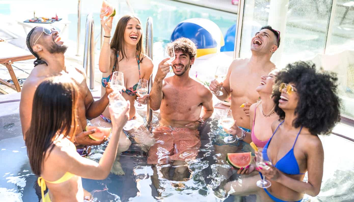 Group of young adults celebrating in a pool.