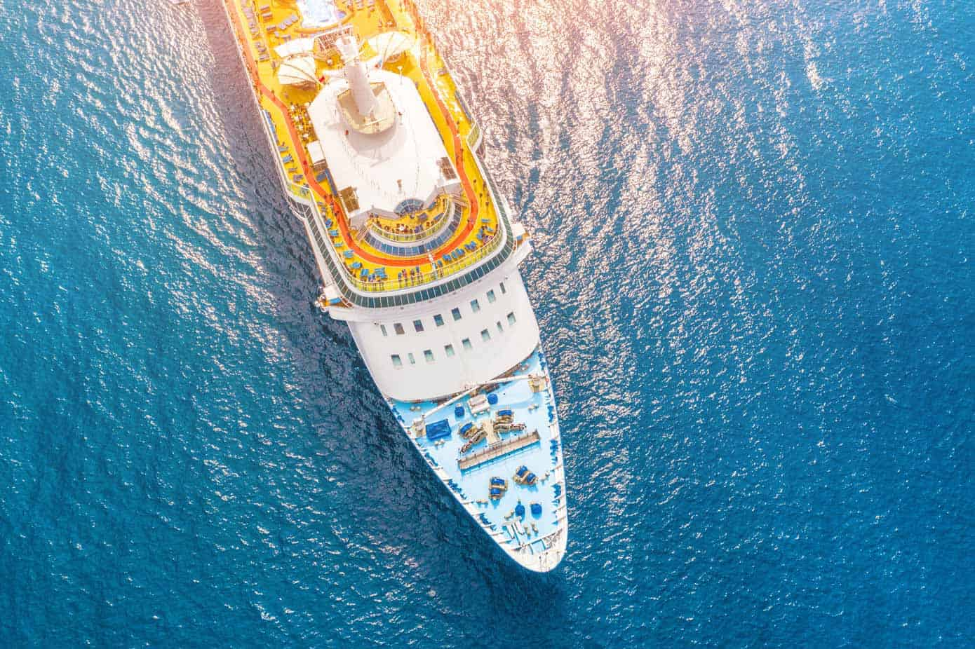 Aerial view of a cruise ship in a turquoise ocean.