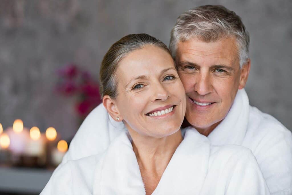 Happy senior older couple inside cruise ship spa with bathrobes on.
