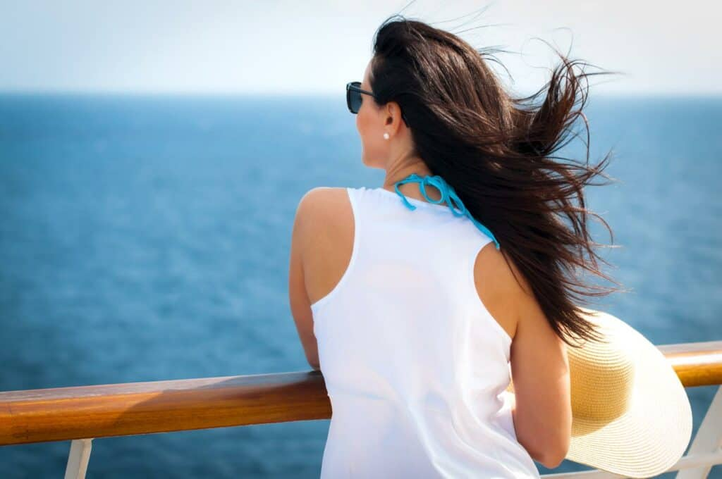 A single woman standing on the cruise ship deck balcony with an ocean view and wind in her hair.