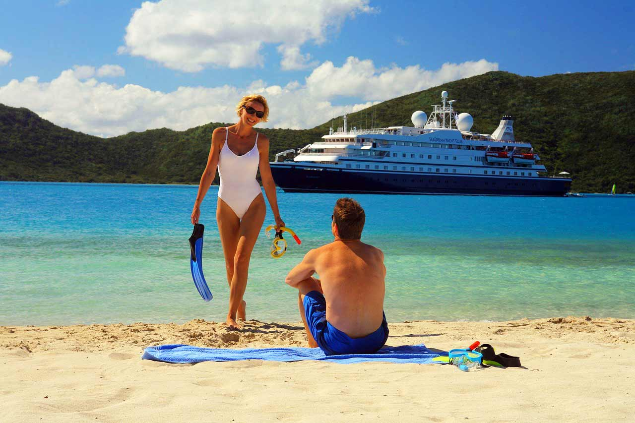 Two adults in front of a cruise ship on the becah.